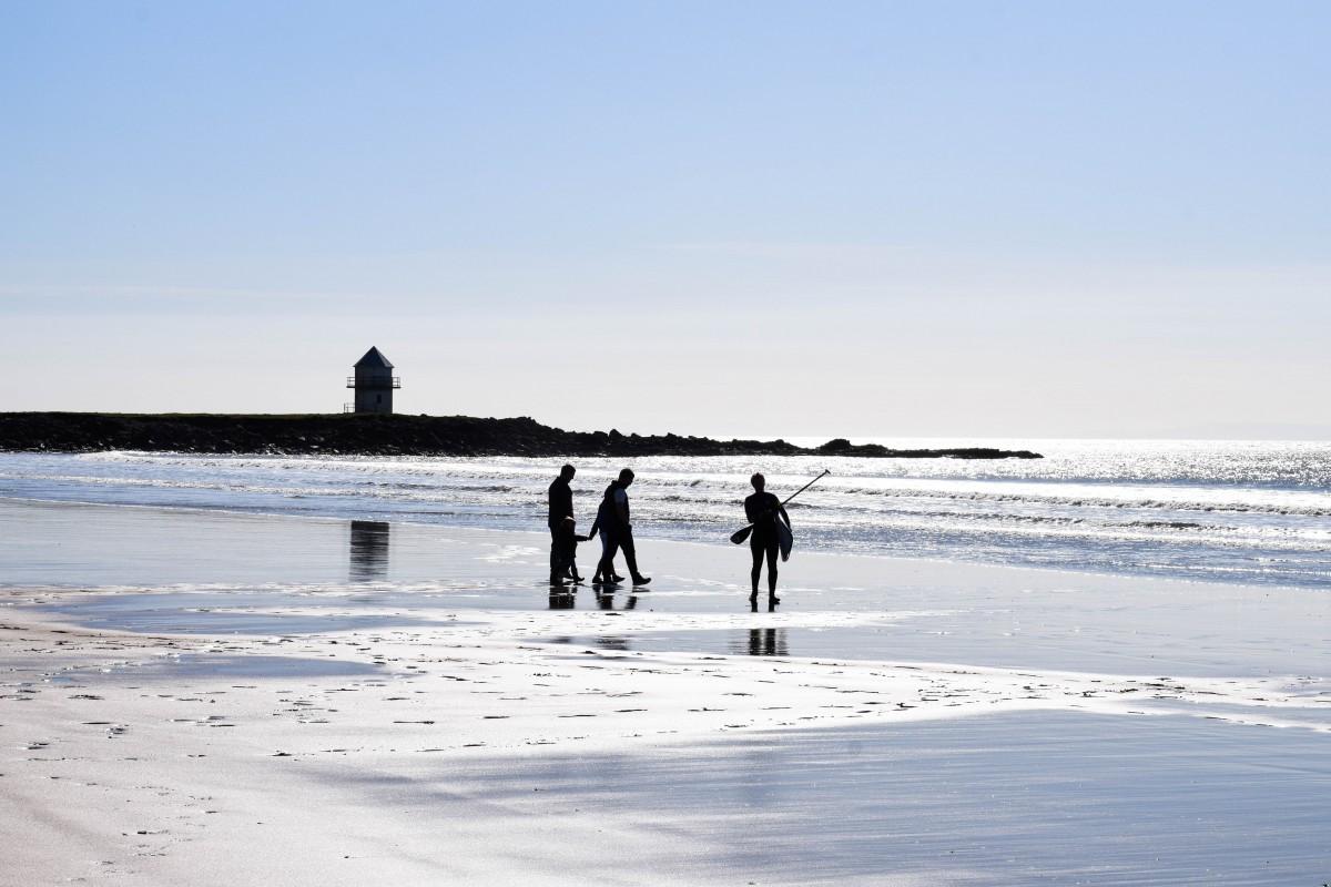 silhoutte surfers on beach
