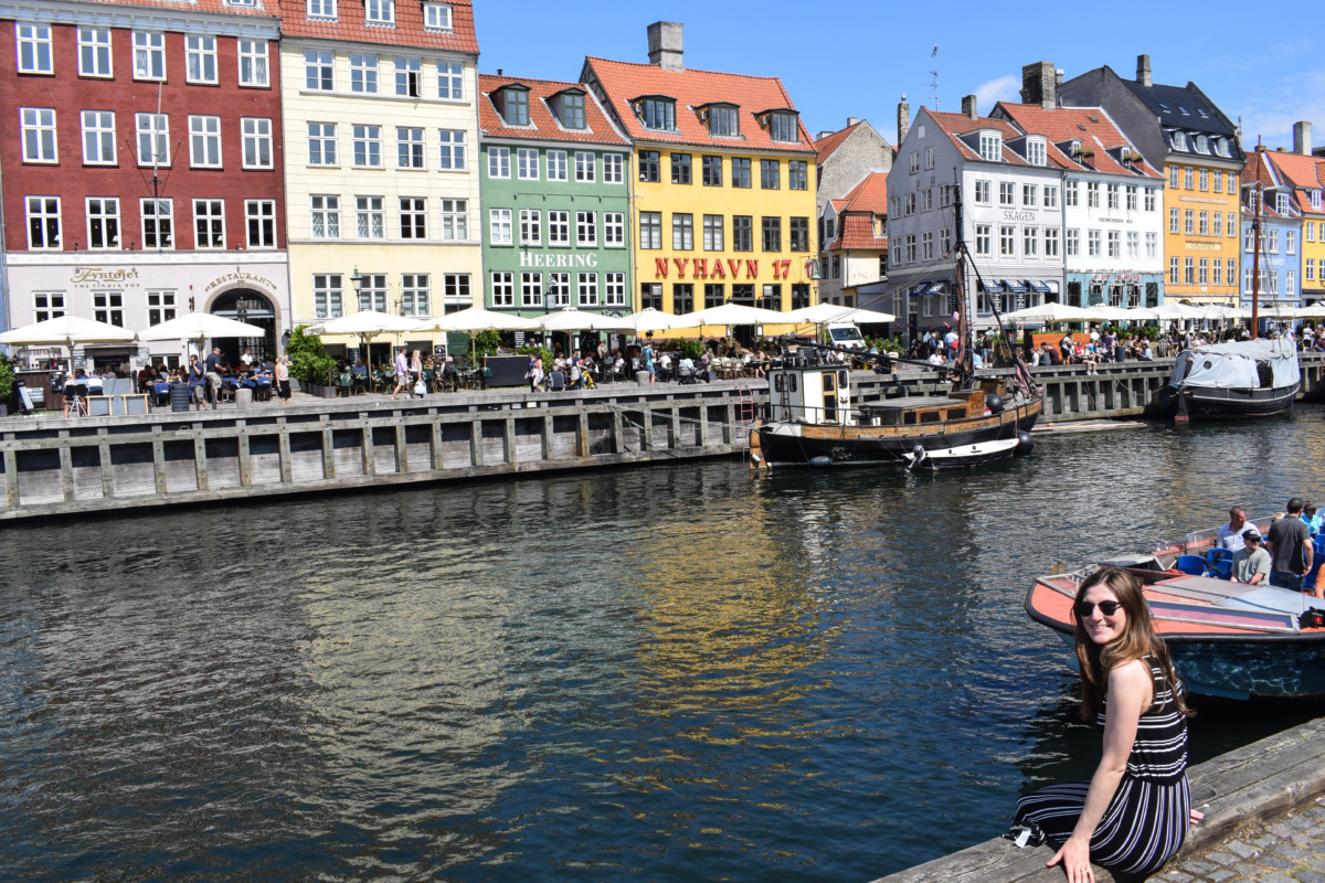 Girl sitting alongside Nyhavn in Copenhagen, Denmark